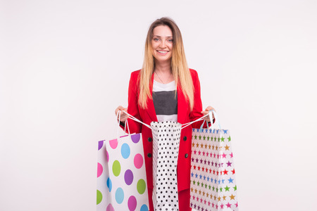 Portrait of young freckled blonde woman with shopping bags on white background