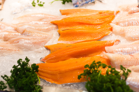 Fresh fish fillets like salmon and cod lay on ice