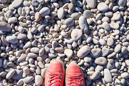 Red sneakers on pebbles, top view