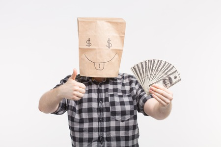 Men in happy paper bag mask with paper bills showing thumbs up on white background