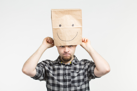 Angry white men wearing happy paper bag mask on white background Stock Photo