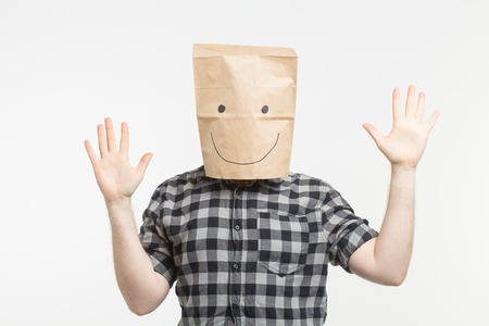 Portrait of man in happy paper bag mask on white background Stock Photo