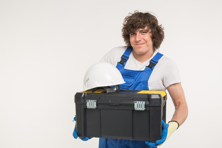 Curly haired builder lifting up toolbox and white helmet in studio.