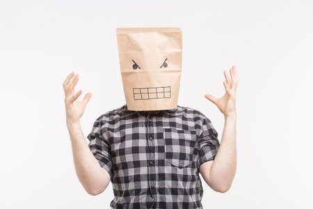 Angry man in paper bag mask on his head raising hands 스톡 콘텐츠