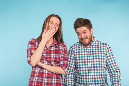 Funny young couple laughing and fooling around together on blue background.