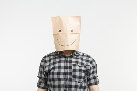 Portrait of men in happy paper bag mask on white background Stock Photo