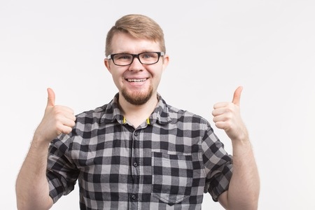 Portrait of young happy man in glasses with thumbs up wearing checkered shirt