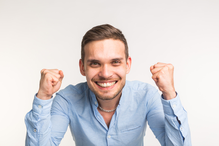 Emotions and people concep t- young happy man raised his fists up over the white background 写真素材
