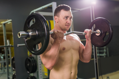 Handsome power athletic man with barbell. Strong bodybuilder with six pack, perfect abs, shoulders, biceps, triceps and chest Stock Photo