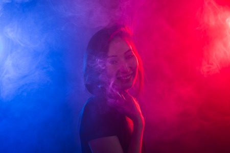 Young woman smoking vape or e-cigarette in neon light Stock Photo