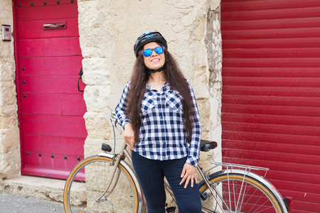 Beautiful young woman with bicycle and helmet in street on sunny day