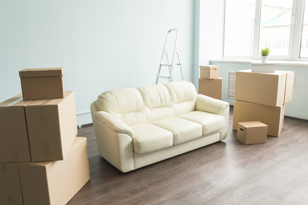 New things, relax, moving, furniture concept - a new white sofa in empty room between an amount of boxes.