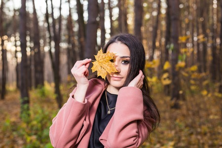 Season, people and nature concept - Woman in autumn park posing and holding the leaf