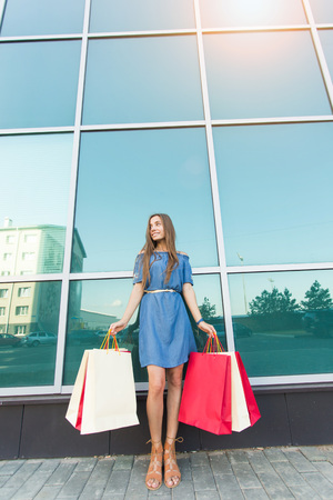 Purchase, sale and people concept young happy smiling woman with shopping bags