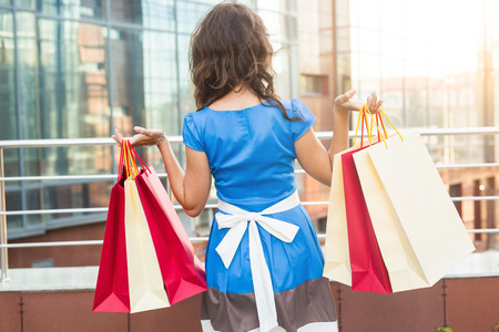 Purchase, sale and people concept - Back view of young woman with shopping bags