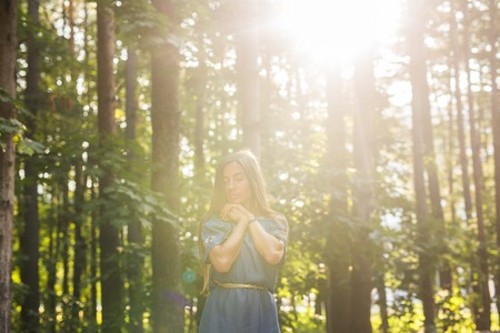 Nature, summer and people concept - Portrait of romantic young woman in forest