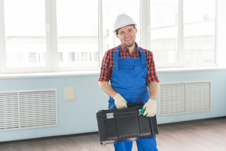 Happy handsome builder with helmet and toolbox laughing at camera.