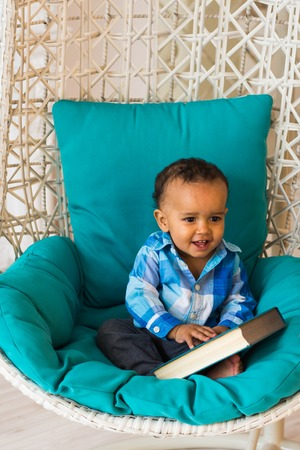 Portrait of African American baby boy holding book on chair
