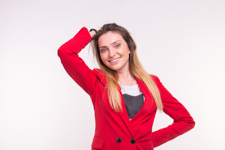 Portrait of smiling freckled beautiful woman wearing red suit on white background