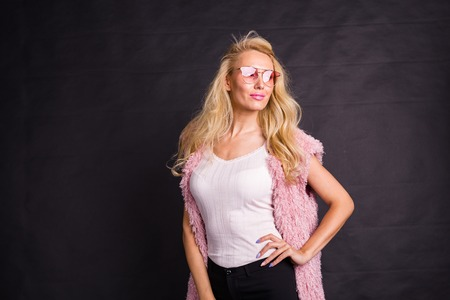 Fashion and beauty concept - portrait of blond model dressed in white shirt and pink cardigan over black background with copy space