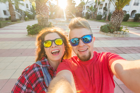 Travel, vacation and holiday concept - Funny couple in sunglasses having fun and taking selfie