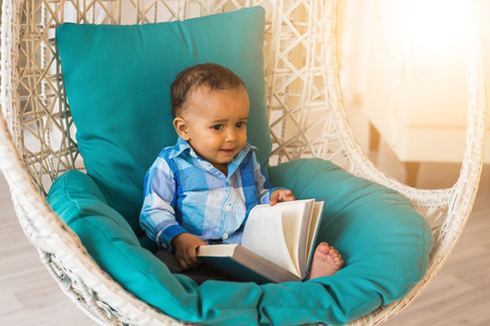 Portrait of African American baby boy holding book on chair. 免版税图像