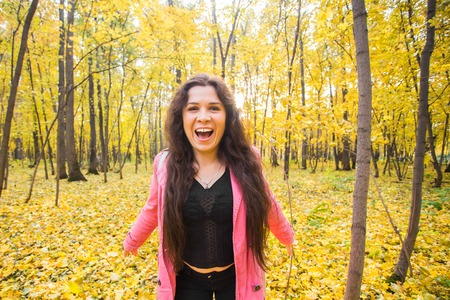 Nature, autumn and people concept - Portrait of young woman in autumn forest in pink jacket Stock Photo