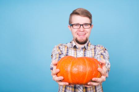 Close up of smiling man holding pumpkins over blue background, harvest concept