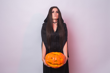 Gothic young woman in witch halloween costume with a carved pumpkin on white background with copy space