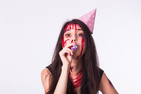 Halloween zombie bloody brunette woman celebrate holidays with whistle on white background