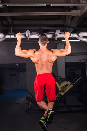 Handsome Muscular Man With Perfect Body Doing Pull Ups in gym