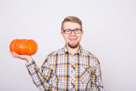 portrait of a young farmer holding a pumpkin on white background Reklamní fotografie