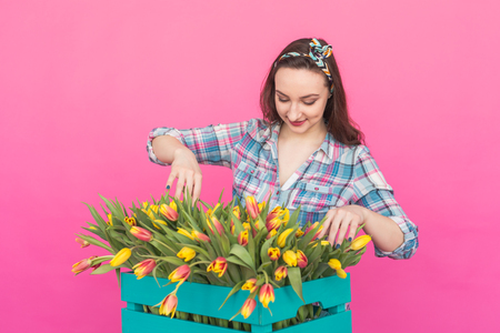 Happy caucasian young woman with box of yellow tulips on pink background Stock Photo