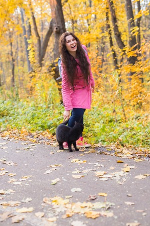 Fall, pets and people concept - woman and black cat are walking in autumn park