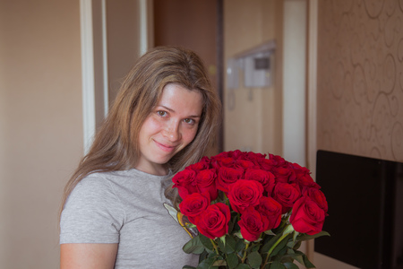 Happy blonde girl with big bouquet of pink roses