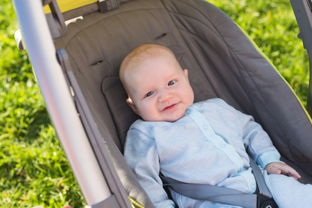 Adorable baby boy sitting in the pram and smiling Stock Photo