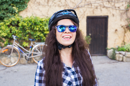 Happy woman with helmet and sunglasses posing backgound bicycle and street