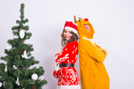 People, family and christmas concept - lovely couple in christmas costumes near christmas tree on white background.