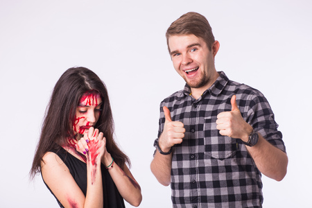 Halloween sad zombie bloody brunette woman and happy laughing man showing thumbs up 스톡 콘텐츠