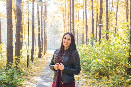 Season, fall and people concept - Portrait of a beautiful brunette woman in autumn nature