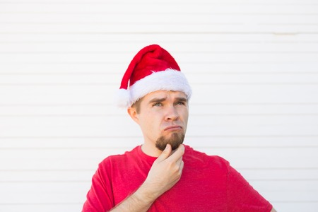 Christmas, people, emotions concept - dissatisfied santa in christmas hat looks up