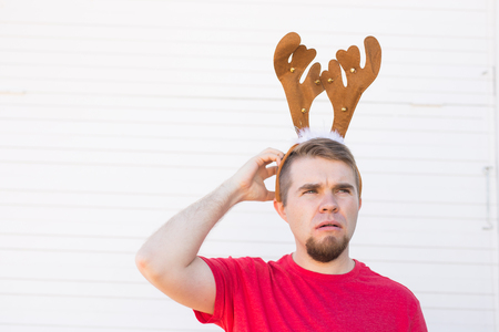 Christmas, holidays and people concept - a mans head with deer horns on it. Man scratches his head Stock Photo