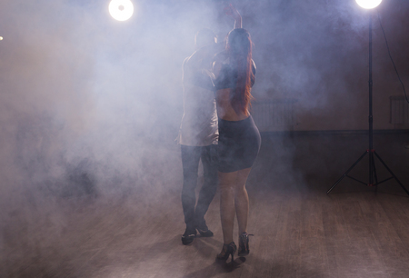 Young couple dancing social danse kizomba or bachata or semba or taraxia in dancing class background.