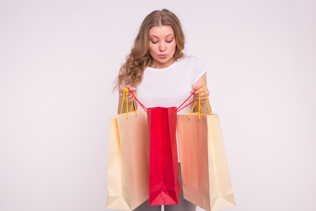 Young surprised blonde woman look into the shopping bag on white background Stock fotó