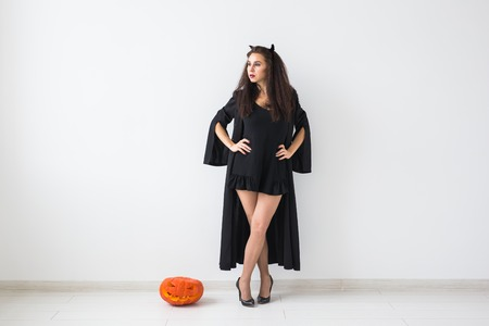 Halloween and masquerade concept - Beautiful young woman posing with Pumpkin Jack-o-lantern over light background with copy space