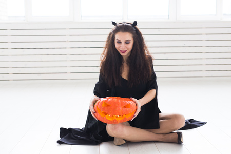 Happy gothic young woman in witch halloween costume smiling over white room background Stock Photo
