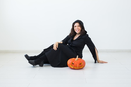 Halloween concept - Happy witch with pumpkin Jack-o-lantern on light background Stock Photo