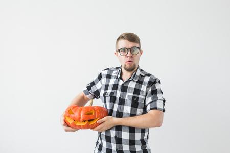 Happy funny man holding a jack o lantern carved halloween pumpkin in light room Imagens