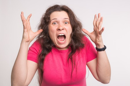 Portrait of a frustrated angry screaming woman screaming out loud on white background Archivio Fotografico
