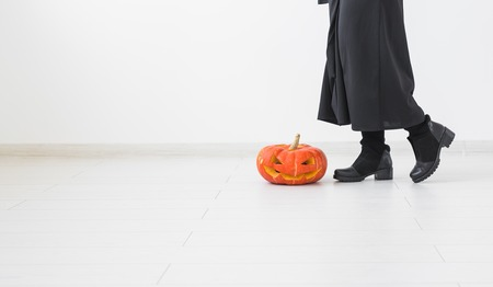 Gothic female in witch halloween costume and Jack-o-lantern over white room background with copy space